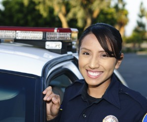 Police woman standing outside of police car